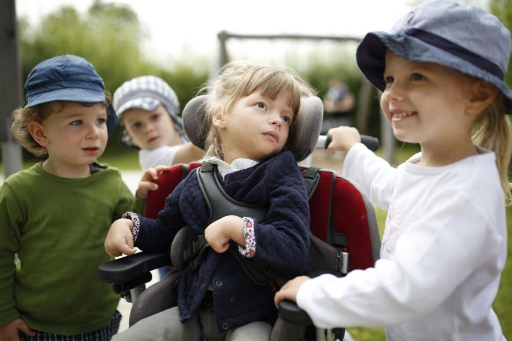 Zwei kleine Kinder am Rollstuhl eines Mädchens mit Behinderung.