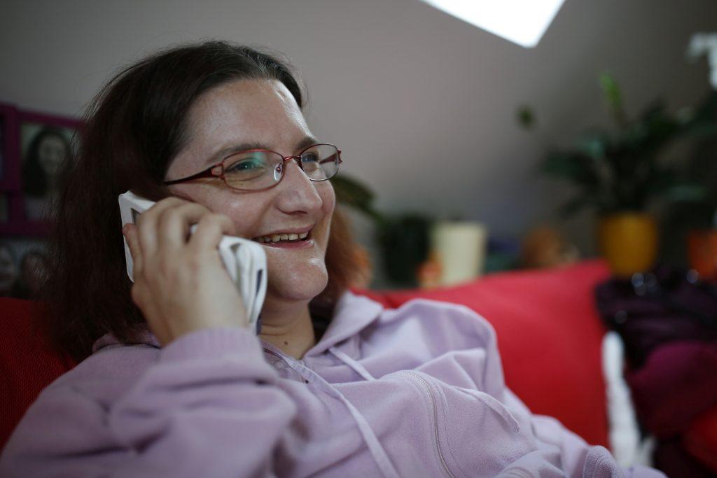 Eine lächelnde junge Frau sitzt auf dem Sofa und telefoniert