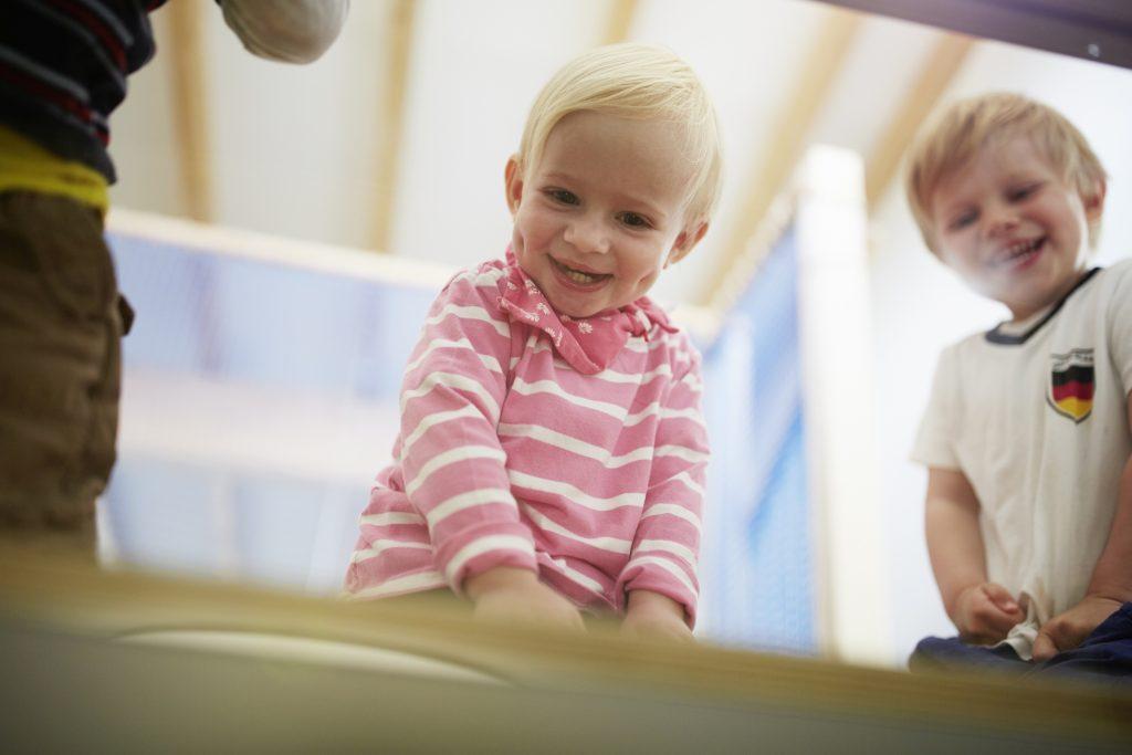 Zwei kleine Kinder die von oben herunterschauen und lachen