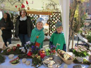 Mehrere Kinder und Erwachsene an einem bunt geschmückten Stand mit Ostersachen