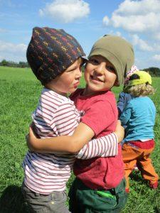 Zwei Kinder auf einer Wiese, die sich umarmen; im Hintergrund spielen weitere Kinder