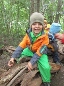 Mehrere Kinder auf einer Baumwurzel, die offensichtlich Spaß im Wald haben