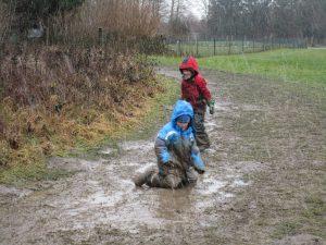 Zwei Kinder, die voller Spaß im Matsch spielen