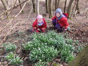 Zwei Kinder in Matschanzügen vor Schneeglöckchen