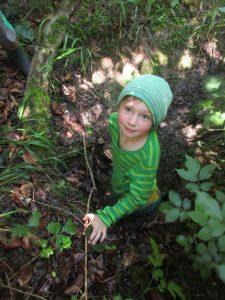 Ein Kind in einer Grube im Wald