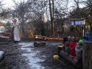 Ein Nikolaus im Freien, im Vordergrund einige Kinder, die auf einem Baumstamm sitzen