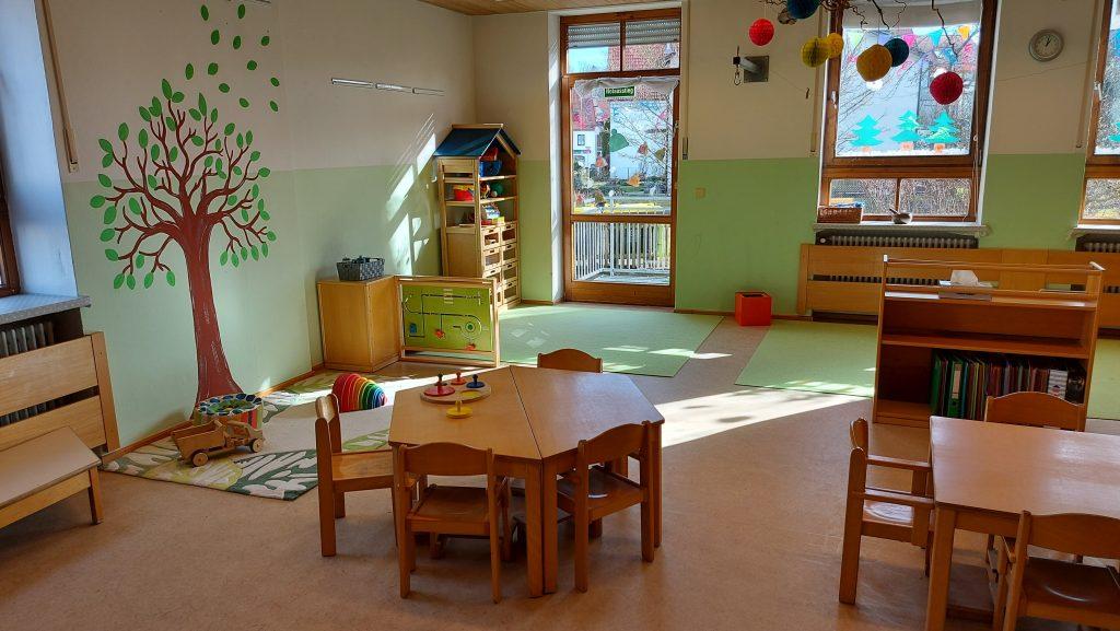 Ein Gruppenraum mit einem Baum an der Wand, verschiedenen Spielmaterialien und kleinen Tischen und Stühlen