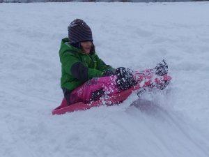 Ein Kind im Winter beim Fahren mit einem roten Schneebob