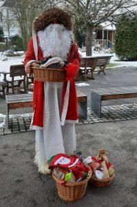 Ein Nikolaus mit einem Geschenkkorb vor sich im Freien